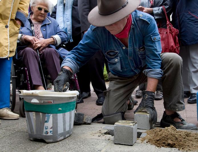 Demnig metselt een struikelsteen in de straat in Doesburg.