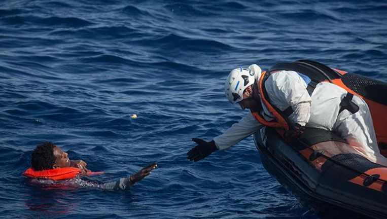 Een reddingswerker redt een vluchteling voor de kust van het Italiaanse eiland Lampedusa in mei 2017