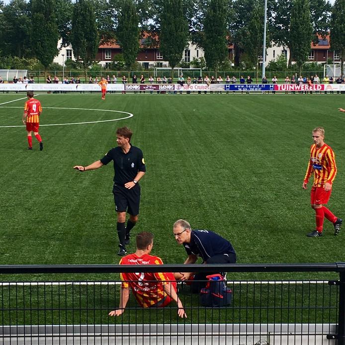 Rick van Beijnen wordt langs de zijlijn behandeld. De verdediger van Juliana'31 viel uit.