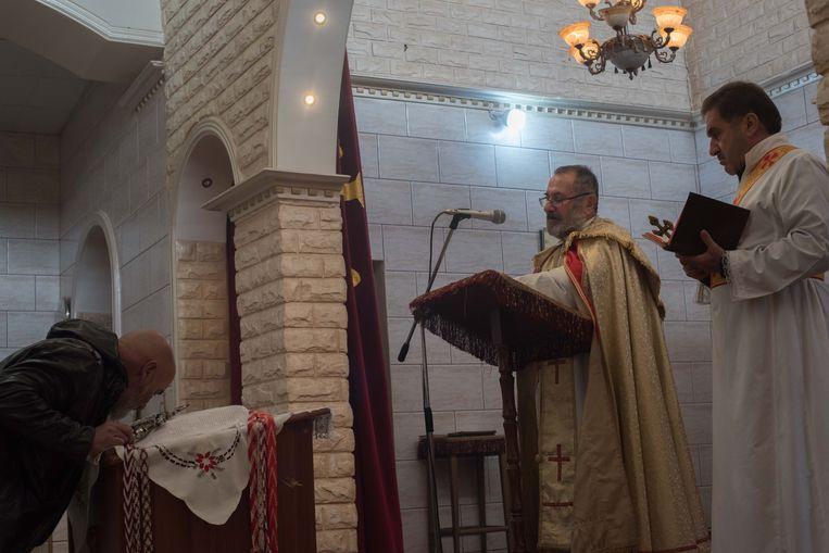 Priester Bachus Ishaya leidt de zondagsdienst in Tel Tamr. Beeld Vincent Haiges