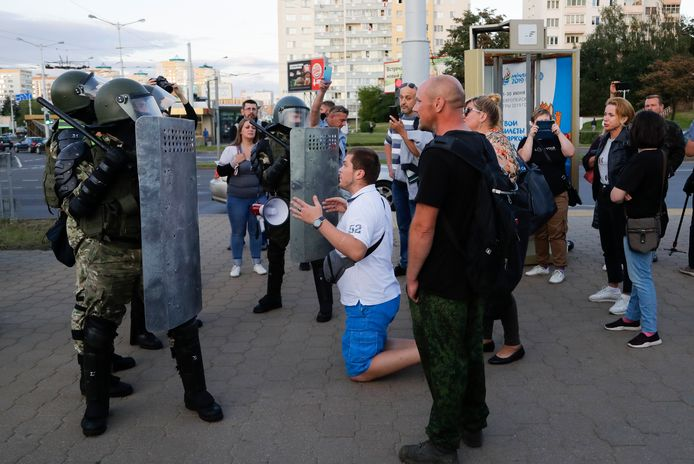 Een man zit op zijn knieën voor de oproerpolitie in de Wit-Russische hoofdstad Minsk. De zwaarbewapende politie was in grote getale aanwezig in de stad, maar dat hield heel wat demonstranten niet tegen om de straat op te komen.