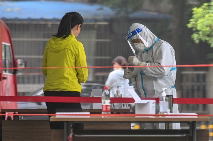 Een zorgmedewerker test een inwoner van Wuhan op het coronavirus.