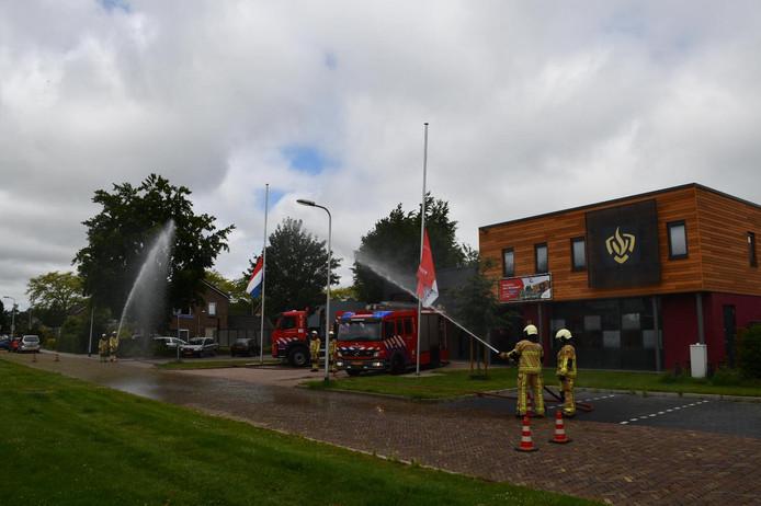 Het brandweerkorps in Vroomshoop geeft het water-ereteken.