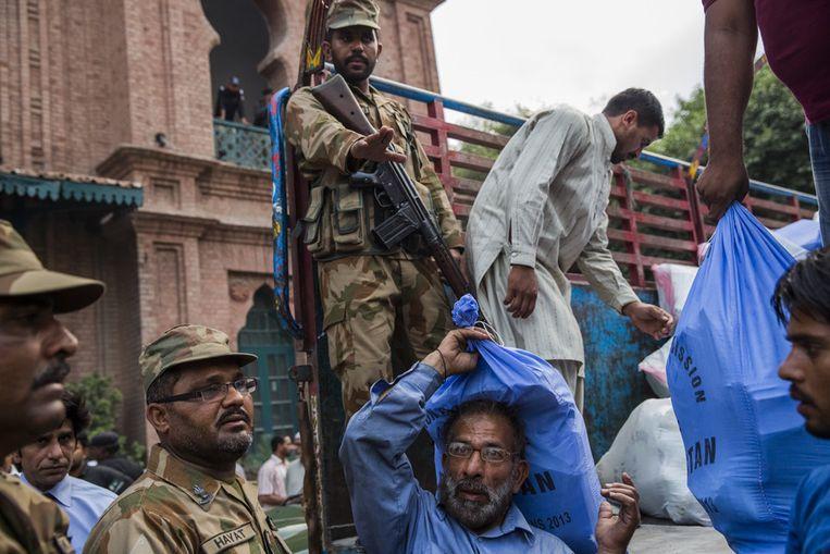 Militairen bewaken de aankomst van stembussen en -biljetten in Lahore, Pakistan. Beeld getty