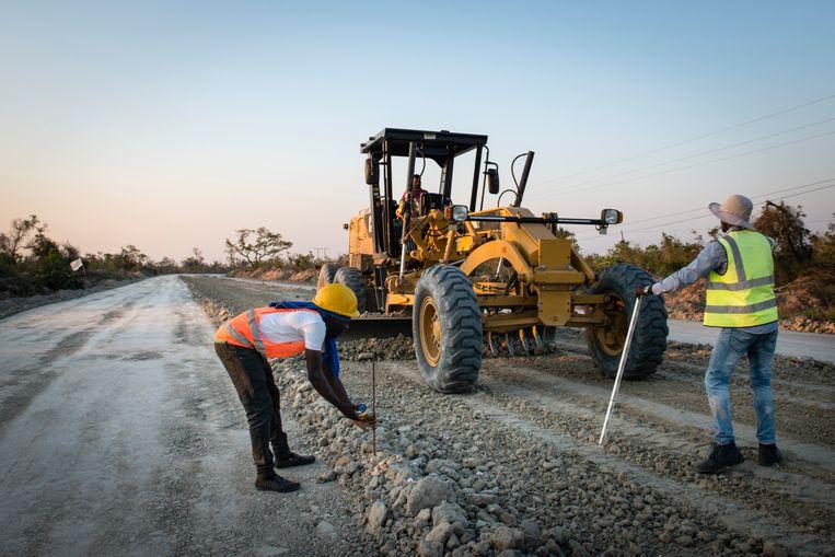 Inmiddels is er op het weer drooggevallen land tussen Beira en Buzi opnieuw een begaanbare zandweg, waarlangs trucks en bouwvakkers weer een echte weg proberen aan te leggen.  Beeld Bram Lammers