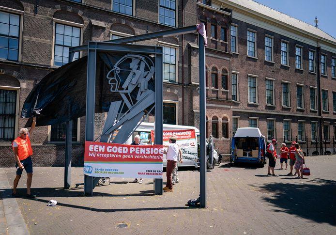 FNV-leden demonstreren bij het beeld van Willem Drees tegen een verslechtering van de pensioenvoorziening.