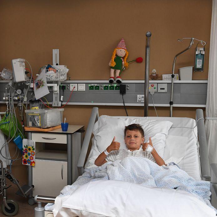 Djerano is alweer aardig opgeknapt na zijn operatie in de Sint MaartensKinderkliniek in Boxmeer. Op de achtergrond staat mascotte Maartje van de kliniek.