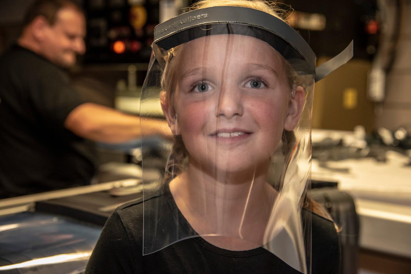 Geert Kuijpers van Kuijpers zeilmakerij en tenten uit Milsbeek heeft sinds de coronauitbraak al heel wat faceshields geleverd. Pien,  de dochter van Geert,  showt het masker.