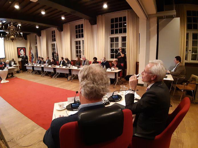 Scheidend burgemeester Hans Verheijen (met glas) luistert naar de mooie woorden die de raadsleden tot hem spreken.
