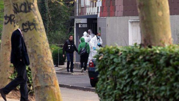 Des membres de la police scientifiques relèvent des indices, le 5 avril 2012 à Grigny, à la sortie du hall d'un petit immeuble où une femme de 47 ans a été la victime d'un tireur.