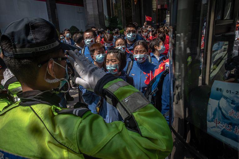 Een politieman groet medische staf uit Shandong. Zij verlaten Wuhan weer nu de epidemie daar over lijkt te zijn.  Beeld EPA