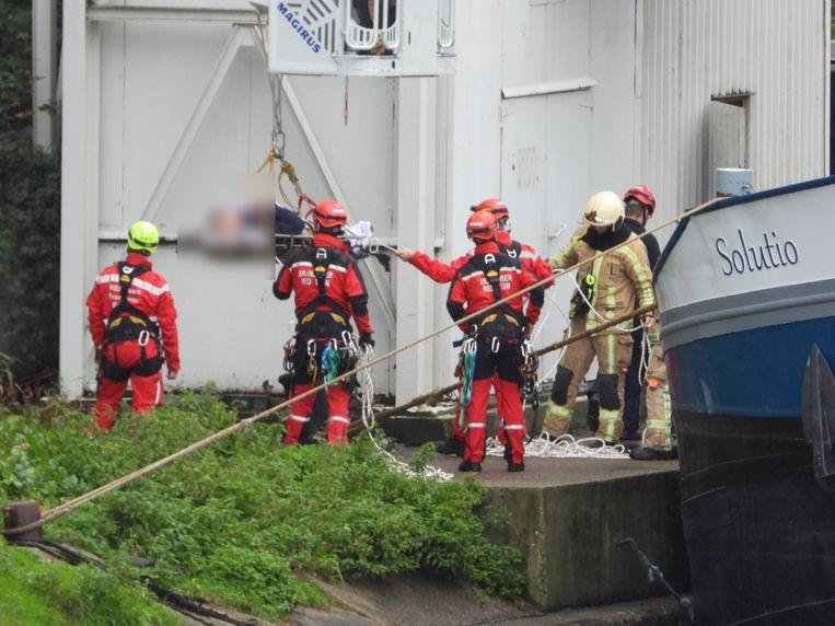 De arbeider wordt met een draagberrie in veiligheid gebracht.