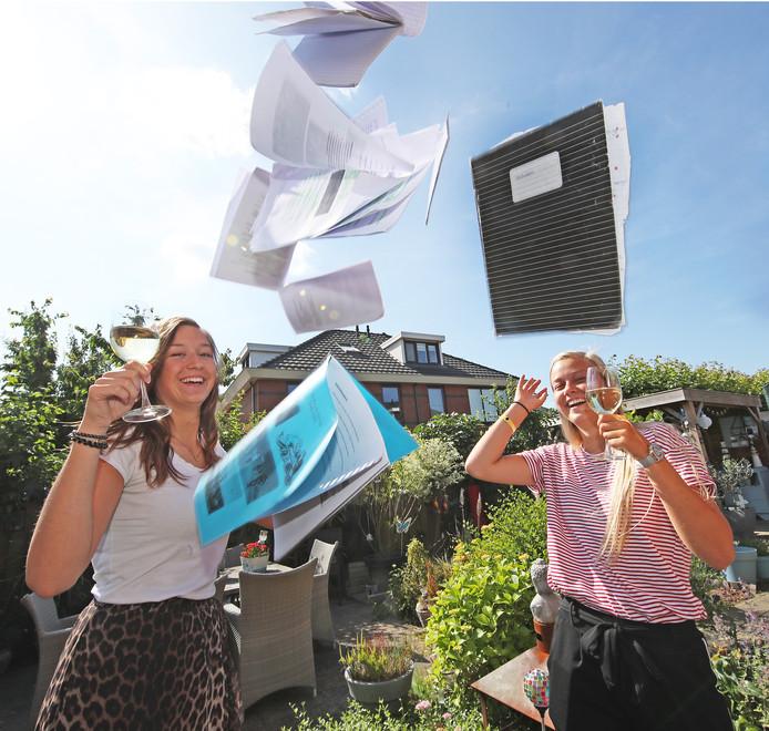 De boeken kunnen de lucht in! Zusjes Kim(l) en Nina Plooij  uit Oude-Tonge vieren dat ze geslaagd zijn.