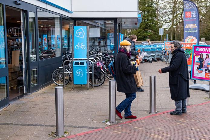 Een klant van Albert Heijn aan de Daalseweg in Nijmegen biedt een dakloze man een broodje aan.