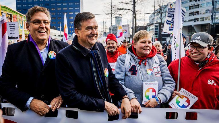 Henk Krol (50 Plus) en Emile Roemer (SP) lopen mee in een mars richting het Malieveld tijdens de landelijke aftrap van het Nationaal Zorgfonds. Beeld anp