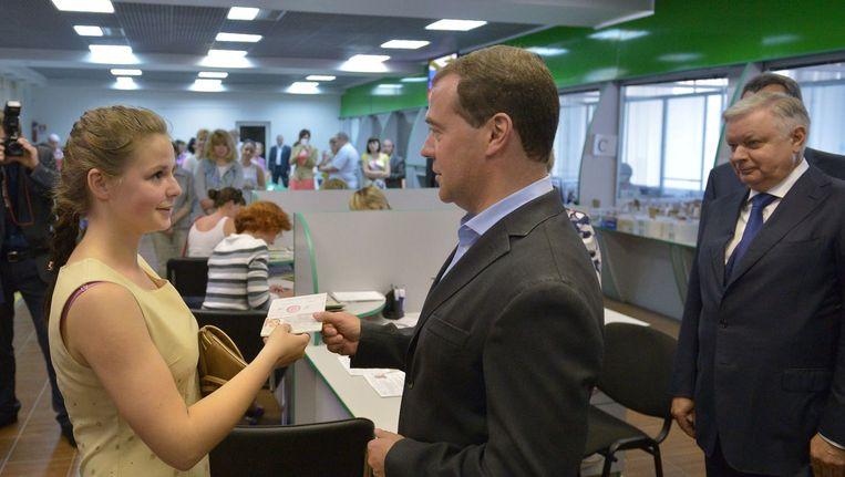 Dmitri Medvedev deelt een Russisch paspoort uit aan een jonge vrouw op de Krim.
