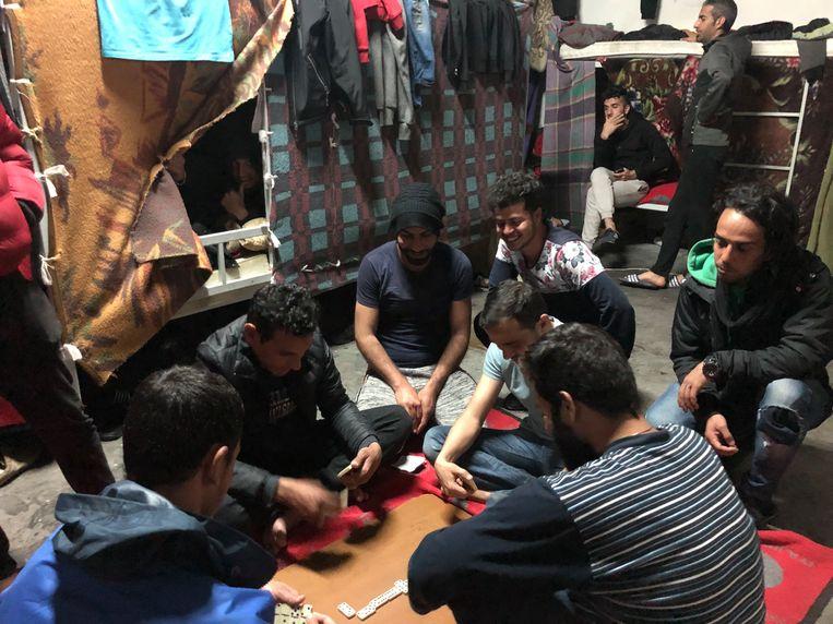 Migranten spelen domino in een voormalige fabriekshal.  Beeld Thijs Kettenis