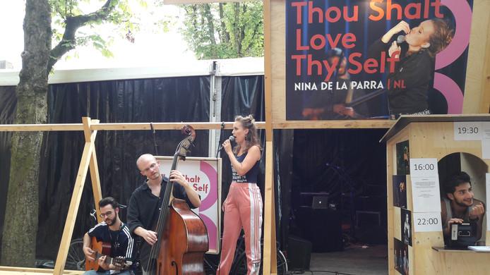 Nina de la Parra probeert al zingend bezoekers van Theaterfestival Boulevard te verleiden tot een bezoek aan de tent waarin ze optreedt.