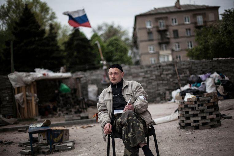Een pro-Russische opstandeling bewaakt de barricade voor het bezette gemeentehuis in Donetsk.