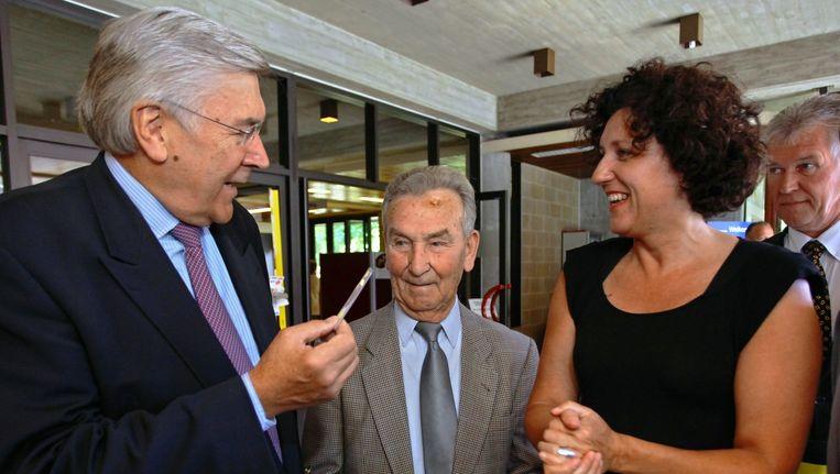 Etienne Schouppe (links) overhandigt Eugène zijn nieuw rijbewijs. Annemie Turtelboom kijkt toe.