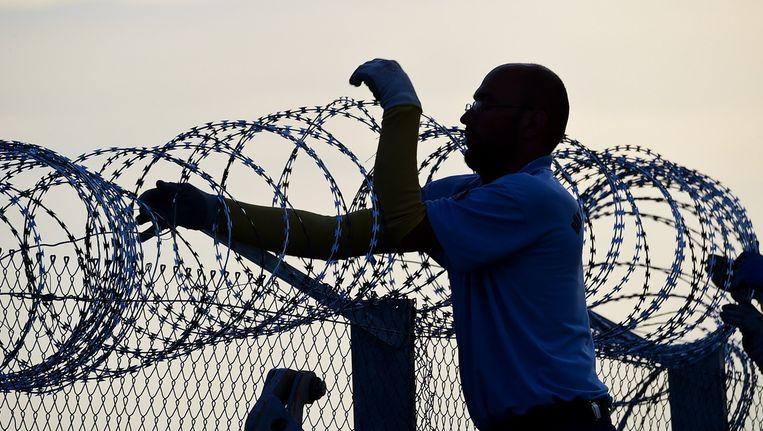 Een man repareert het hek bij de grens tussen Servië en Hongarije. Beeld afp
