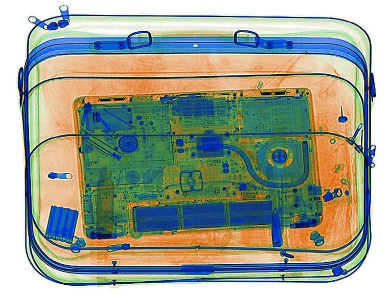 Een beeld van een tas met een laptop uit een veiligheidscanner op een vliegveld.  Beeld REUTERS