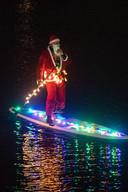 De kerstman op een versierde kano van de Batavieren in het Maas-Waalkanaal.