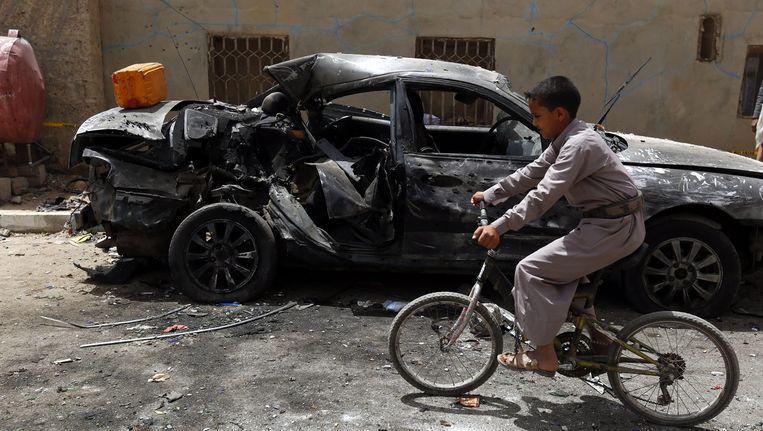 Een jongen fietst langs een verwoeste auto, een dag na de aanslag op een moskee in Sana'a Beeld epa