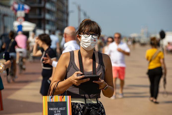 Een vrouw draagt een mondmasker op de zeedijk in Knokke-Heist. Nee, jodium in de zeelucht remt het virus niet af en nee, het dragen van een mondmasker zal je geen zuurstofgebrek opleveren.