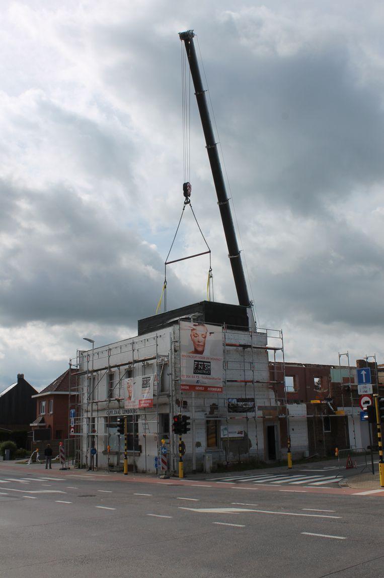 De kraan plaatst de containers in de voormalige feestzaal.