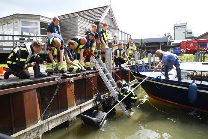 Klaas Klos (rechts met pikhaak) helpt de brandweer om de scootmobiel uit het water van de Bovenhaven in Kampen te tillen. Met diezelfde pikhaak redde hij even daarvoor het leven van de scootmobieler.