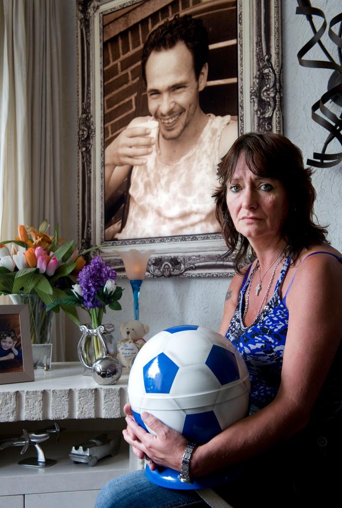Moeder Alie Mesu met een portret van haar vermoorde zoon Richard Houtveen, met urn op schoot.
