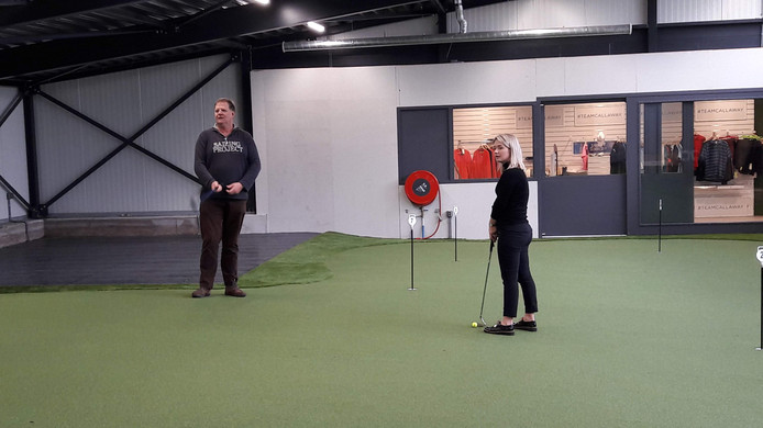 Manager Nienke Brosens en eigenaar Toine Berkelmans van Golfcentrum Roosendaal oefenen op de overdekte putting green.