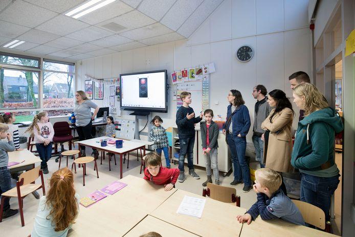 Daan (rechts naast digibord) vertelt belangstellende ouders over hoe alles reilt en zeilt op De Prinsenakker in Bennekom.
