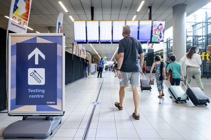 Reizigers bij de teststraat op Schiphol, die dit weekend sluit