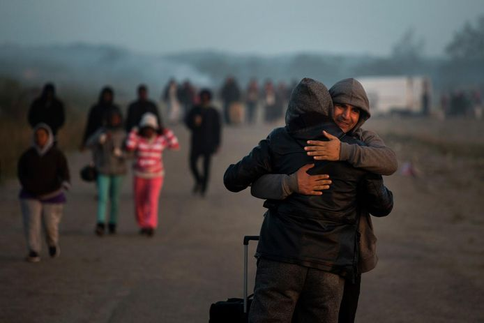 Twee mannen nemen afscheid terwijl ze het kamp verlaten.