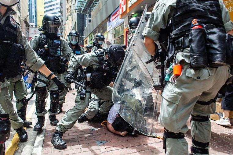 De oproerpolitie in Hongkong drukt een demonstrant tegen de grond die protesteert tegen een omstreden nieuwe veiligheidwet, eerder deze maand. Beeld SOPA Images /LightRocket via Gett