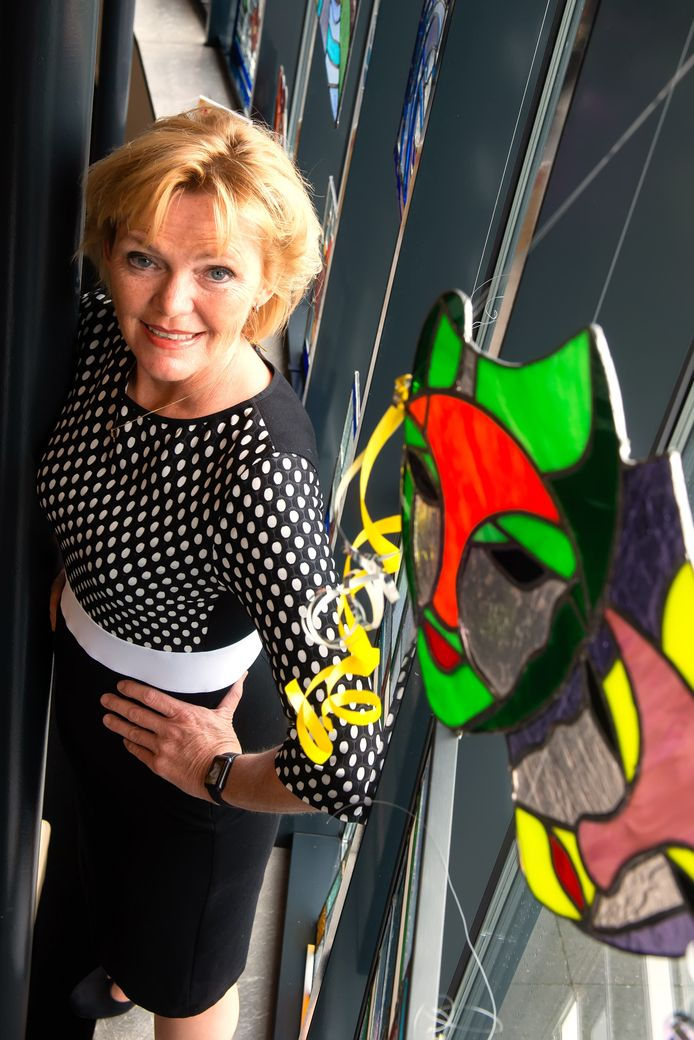 Hilda Vliegenthart bij het kunstwerk Twee Maskers, dat cursiste José Dekkers maakte tijdens een cursus bij Nieuwe Nobelaer. Deze en andere glaskunst is nu te zien in de bibliotheek.