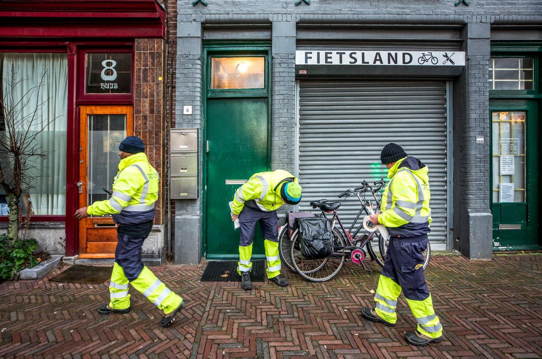 Handhavers controleren in het centrum van Amsterdam op verkeerd gestalde fietsen.  Beeld null