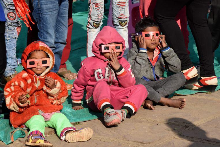 Ook de allerkleinsten bewonderen de zonsverduistering in Bhopal in India.