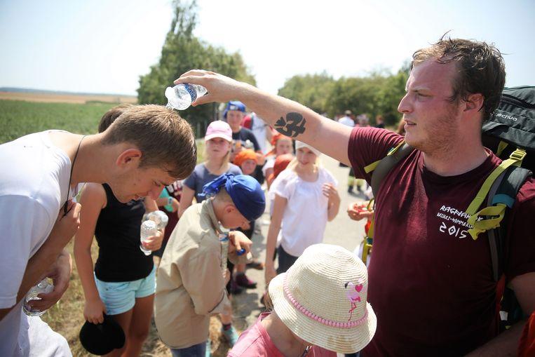 Scoutsleider Paul krijgt van een collega-leider snel een kleine waterdouche om af te koelen nadat hij met de groep een paar uur vast zat op een Thalys-trein in Marcq.