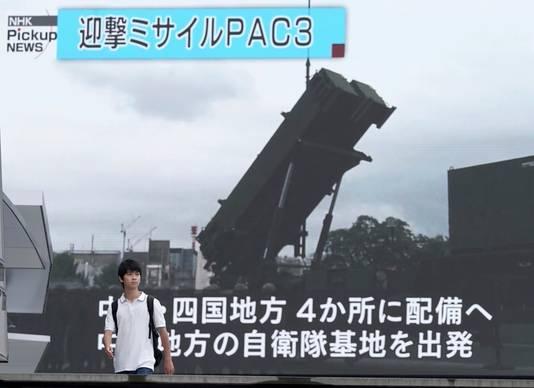 Een Japanse jongen loopt langs een televisiescherm waarop beelden van een Amerikaanse PAC-3 Patriot-installatie die Japan moet beschermen tegen raketten uit Noord-Korea.