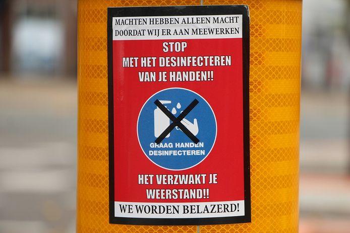 Stop met desinfecteren van je handen-oproepje op verkeerszuil.