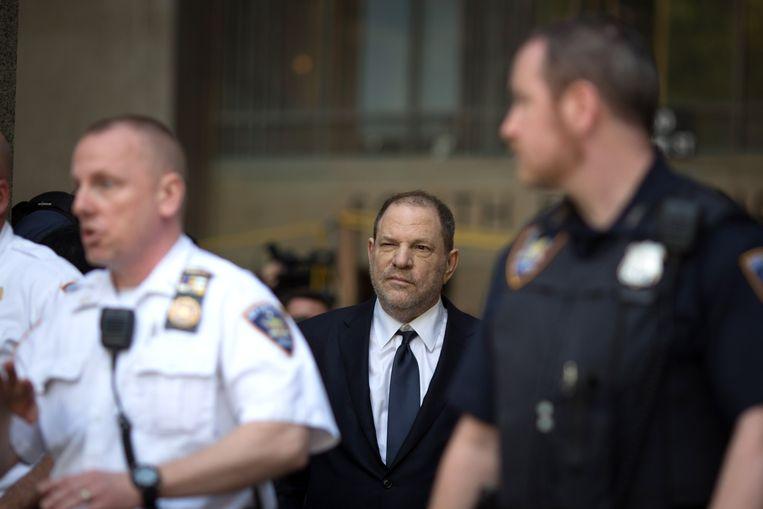 Harvey Weinstein wordt begeleid door politie-agenten bij de rechtszaal. Beeld Getty Images