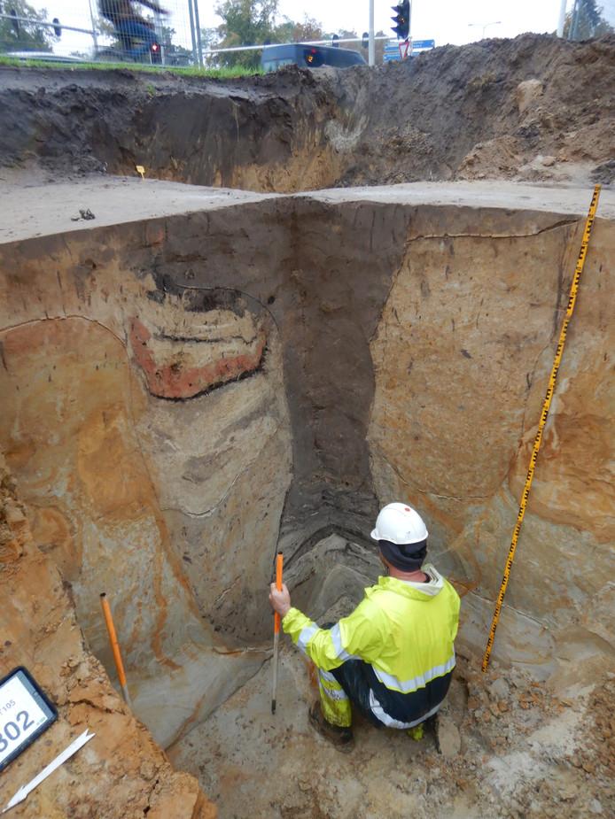 Bij de archeologische opgravingen in Tilburg (Trouwlaan/Ringbaan -Zuid) werd een drie meter diepe waterput aangetroffen, zichtbaar door de donkere aarde in de gele grond.