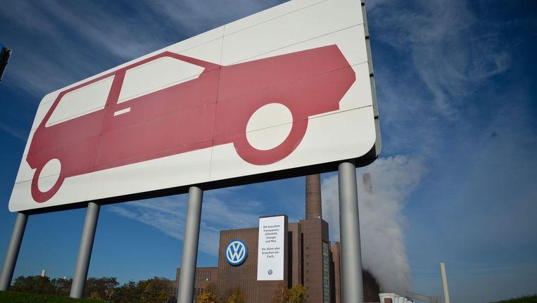 Een bord met de tekst 'We hebben transparantie, openheid, energie en moed nodig. Maar vooral hebben we nodig: jou' hangt naast het Volkswagen-logo op de Volkswagen-fabriek in Wolfsburg. Beeld epa
