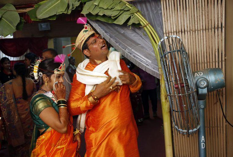 Een net getrouwd stel staat voor een ventilator tijdens hun huwelijksfeest in Mumbai. Beeld ap