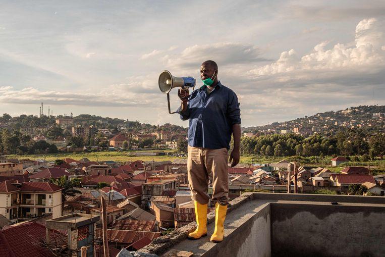Gonzaga Yiga (49) op het hoogste gebouw van Kampala, de hoofdstad van Oeganda. Met een megafoon roept hij elke ochtend en avond adviezen rond waarmee de inwoners van de stad de verspreiding van het coronavirus tegen kunnen gaan.   Beeld Badru KATUMBA / AFP