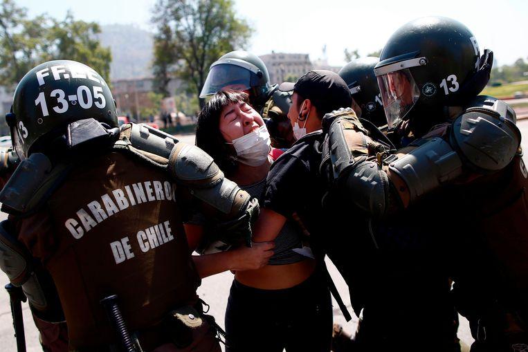 Agenten pakken een demonstrante op in de Chileense hoofdstad Santiago.