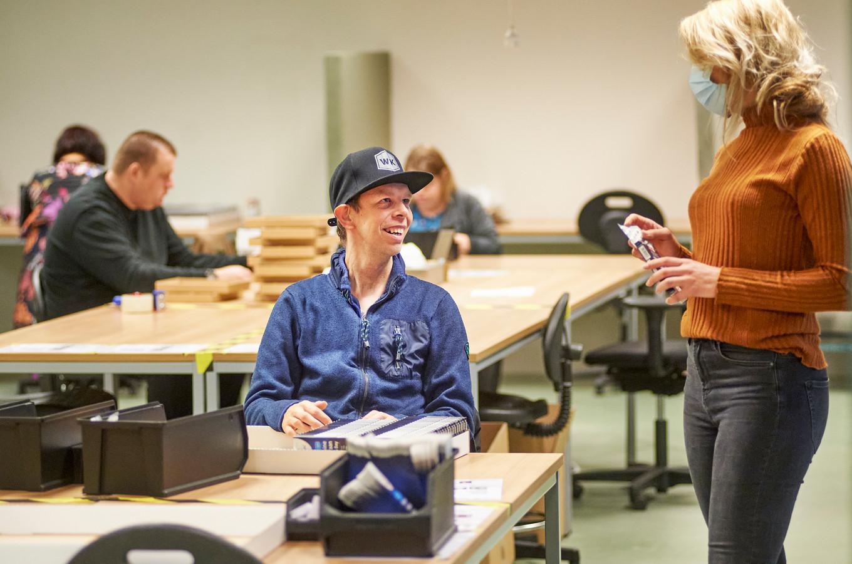 Melvin van Meurs ( op zijn werkplek bij Werkkracht in Oss. Hij is bang om bij een lockdown thuis te komen zitten.  Rechts zijn begeleidster.